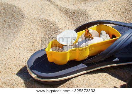 A Blue Flipflop Sandal Lies In The Fine Sand. On It Lies A Yellow Lighthouse Children Sand Mold, Fil