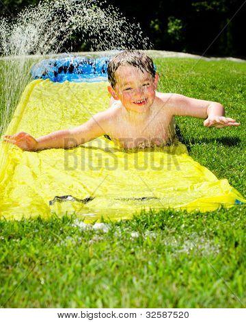 Criança feliz na lâmina de água para se refrescar em um dia quente durante a Primavera ou Verão