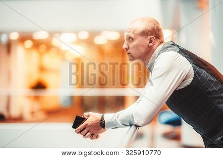 Sideview Of A Confident Handsome Adult Man Entrepreneur Leaning Against A Chromium Railing In The Of
