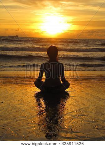 Young Woman Sitting On The Beach, Silhouette At Sunset. Young Woman Practicing Yoga Outdoors. Harmon