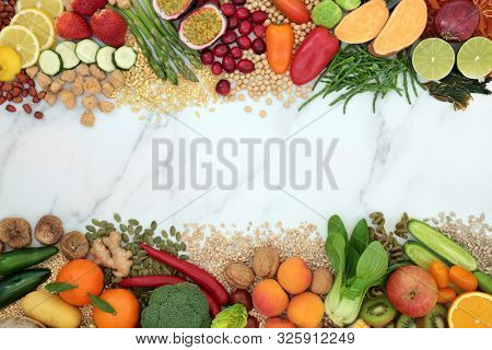 Vegan health food background border with a large collection of foods. High in protein, vitamins, minerals, antioxidants, fibre, anthocyanins, omega 3 and smart carbs. Ethical eating food concept.