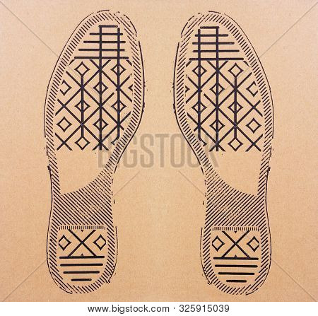 Imprint Soles Of Sneakers On Cardboard Sheet. Imprint Soles Shoes - Sneakers On Cardboard Background
