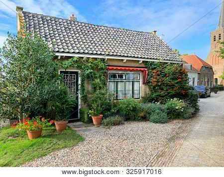 Charming Dutch brick house with the protestant church in the background. Het Woud, Zuid-Holland, the Netherlands.