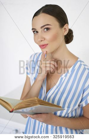 Mirthful Book Lover Touching Her Chin Stock Photo