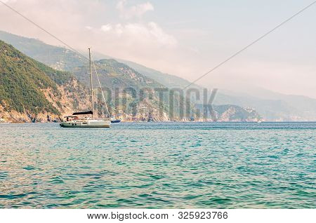 Monterosso Al Mare, Italy - September 02, 2019: Sea Yachts Near The Rocky Coastline With Green Mount