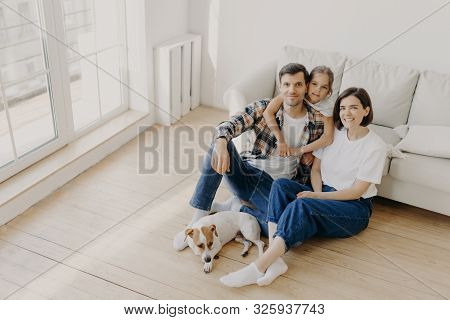 Lovely European Family Of Father, Mother And Their Daughter Sit On Floor Near Sofa In Spacious White