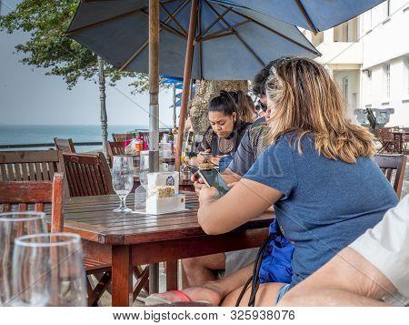 Rio De Janeiro, Rj. September 11, 2019. Custommers At The Copacabana Fort Cafe Consulting Their Smar