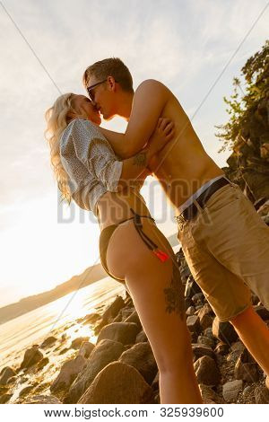 Tilt Shot Of Young Couple Smooching At Beach
