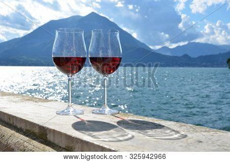 Two wine glasses against lake Como, Italy