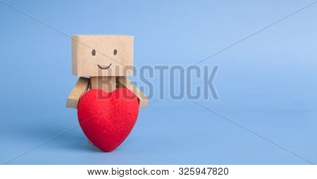 Love And Technology Concept. Cute Little Robot Embracing Red Heart, Blue Panorama Background With Fr
