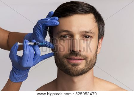 Male Injective Cosmetology. Middle Aged Man Receiving Wrinkle-removing Injection Over White Studio B
