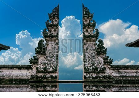 Young Couple Standing In Temple Gates And Holding Hands Of Each Other At Lempuyang Luhur Temple In B
