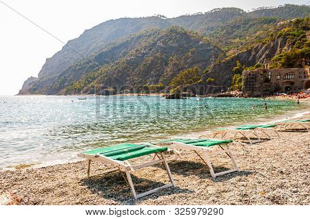 Monterosso Al Mare, Italy - September 02, 2019: Green Deck Chairs On Pebble Beach With Green Mountai