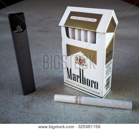 Juul Vape Pod Electronic Cigarette Device With A Pack Of Marlboro Cigarettes And One Cigarette Place