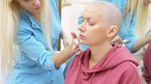 stylish bald woman at a beautician appointment. applying anesthetic cream to the face poster
