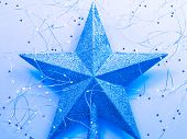 Christmas greeting card. Flat lay of sparkling star topper and LED string lights arranged on blue background. poster