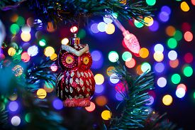 Close-up Of A Shiny Christmas Decoration In The Form Of A Red Owl Hanging On A Christmas Tree In The