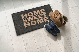 Home sweet home doormat at condo door entrance with couples pairs of shoes moving in together. women's sneakers and man's boots on floor, new apartment.