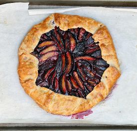 Rustic Homemade Plum Galette On Parchment Paper. Flat Lay,top View.