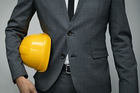 Safety At Work Or Construction Business Concept - Businessman Holding Yellow Helmet Underarm