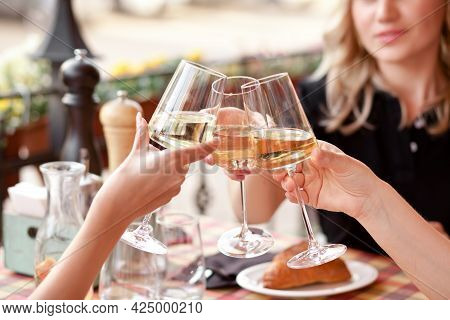 Hands Holding The Glasses Of White Wine Making A Toast. Woman Cheers.