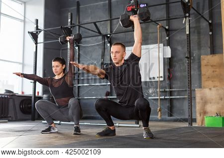 Attractive Sports People Are Lifting Dumbbells Together At Crossfit Gym. Healthy Lifestyle Concept.