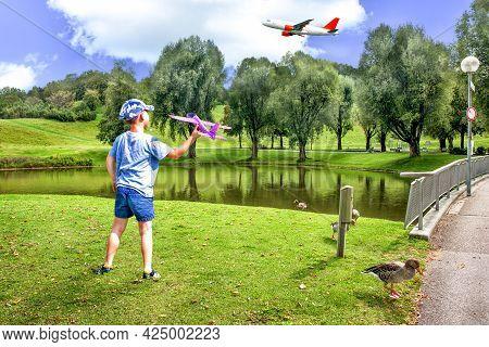 A Boy Launching A Toy Aeroplane On A Green Lawn.