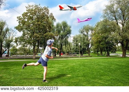 A Boy Launching A Toy Aeroplane On A Green Lawn And An Aircraft In The Sky.