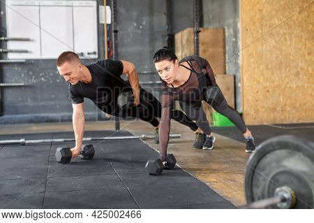 Confident Couple Working Out With Dumbbell In A Gym.