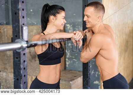 Portraitof A Loving Couple In Gym. Man And Woman Look At Each Other And Smile.