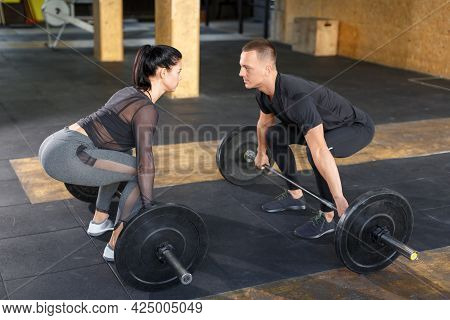 A Man And A Woman In The Gym Look At Each Other Before Doing A Barbell Snatch.