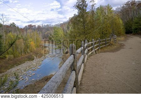 Footpath With Fences In Autumn With The River Valley In The Background