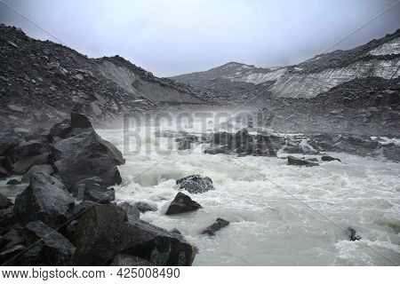 Akkem Glacier In Altai With A Turbulent River And Stones In Bad Weather, Belukha. A Stormy Stream Of