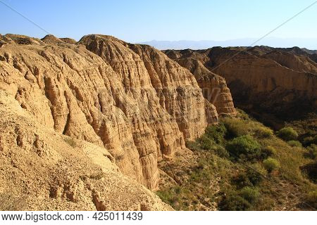 The Relief Ribbed High Wall Of The Lunar Canyon In Altyn-emel In The Sunlight At Sunset, At The Foot