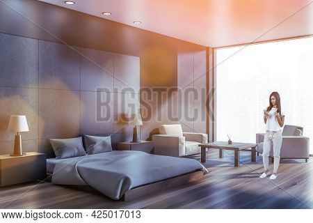 Attractive Woman In Cozy Home Wear Browesing Internet Using Smart Phone In Modern Panoramic Studio A
