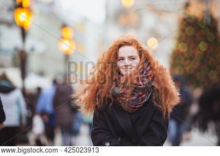 Red Hair Girl Enjoying European Christmas Market. Blurred Lights On Christmas Tree On Background