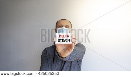 Covid-19 Delta Strain Symbol. White Card With Words 'delta Strain'. A Young Man In A Grey Wear And M