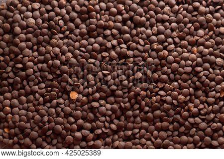 Background Of Red Lentils. Scattered Lentils. One Split Lentils Against A Whole Background