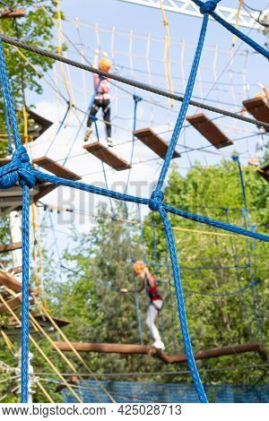 Fragment Of A Rope Park With An Obstacle Course With Blurred Images Of Climbing People In The Backgr