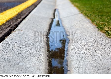 Flowing Rainwater In The Canal Is A Cement Ditch Of A Drainage System On The Side Of Wet Asphalt Roa