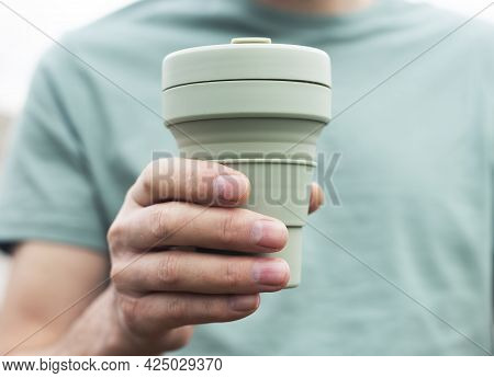Reusable Eco Cup For Takeaway Coffee. Male Hand With Sustainable Silicon Tea Mug. Eco-friendly Perso