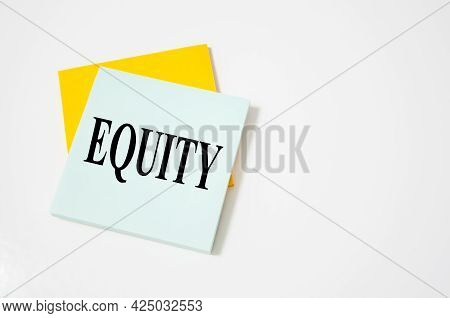 Text Equity Text Written On A White Notepad With Colored Pencils And A Yellow Background