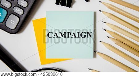 Campaign Word Written On Yellow Sticker And White Background Near Office Supplies. Word