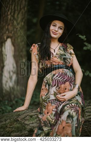 Close Up Of Pregnant Likable Caucasian Woman 25-30 Year Old Wearing Colorful Dress And Black Hat Pos
