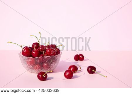 Glass Bowl Full Of Fresh And Juicy Cherries On A Pink And White Background. Place For Your Text. Sea