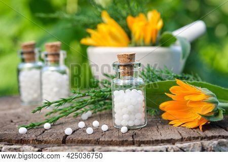 Bottle Of Homeopathy Granules. Homeopathic Remedy - Calendula. Calendula Flowers And Juniper Twigs.
