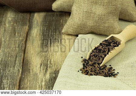 Cumin And Black Sesame Seeds In A Wooden Spoon. Wooden Background With Copy Space
