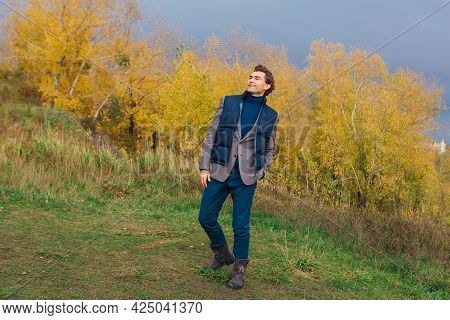 Tall Handsome Man Outdoor In Autumn Forest On The Hill