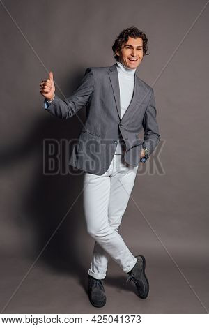 Tall Handsome Man Dressed In White Turtleneck, White Jeans And Grey Jacket Posing On The Grey Backgr