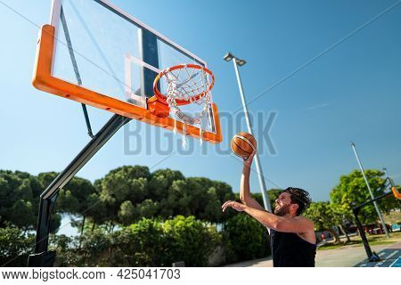 Male Sportsman Playing Basketball Throwing The Ball At Playground, Doing Successfully Slam Dunk View